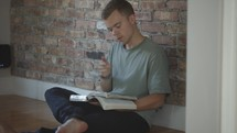 young man sitting on the floor reading the Bible