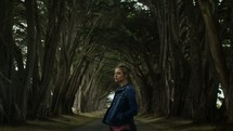 a woman standing in the middle of a tree lined road