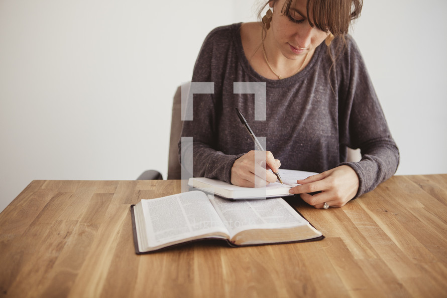 woman at a Bible study writing in a journal and reading a Bible