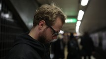 man reading a Bible while waiting in a subway station