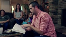 a man reading a Bible to a small group at a Bible study