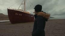 woman walking by an abandoned rusty ship