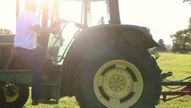 a farmer getting in a tractor
