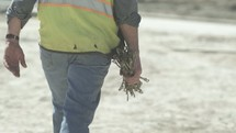 construction working carrying metal cables