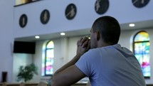 a man in prayer in a church