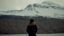 a woman looking out at a snow covered mountain