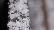 snow falling on a railing