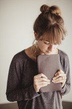 woman holding a Bible with her head bowed in prayer