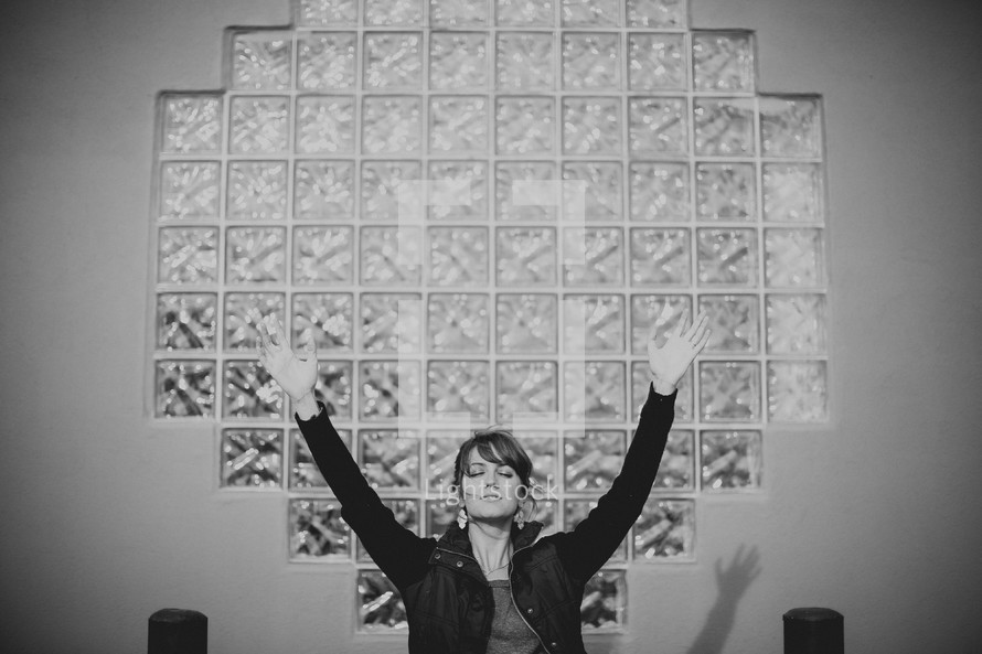 woman in front of glass box windows with her hands raised in worship to God