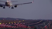 Airplane landing on a runway at night.