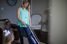 a woman vacuuming while her children watch tv