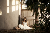 bride sitting on the ground outdoors in front of a door