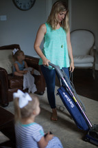 a mother vacuuming while daughters watch tv