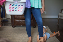 a mother with a laundry basket and daughter hanging on to her leg