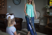 a mother vacuuming while daughter watches tv