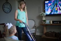 a mother vacuuming while child watches tv