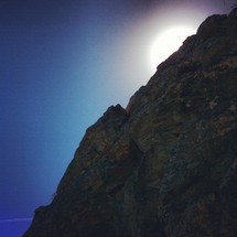sun moving behind a rock peak