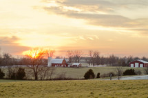 A field with barns and a sunset.