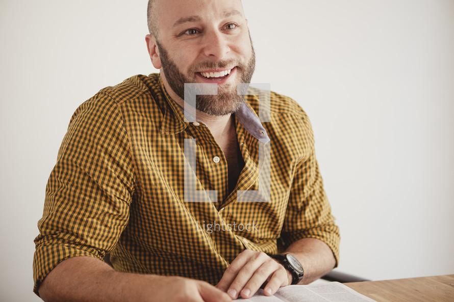 man smiling reading a Bible