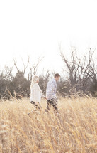 couple holding hands walking through a field
