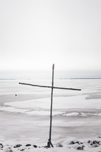 wooden cross by a frozen lake