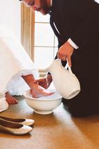 a groom washing his brides feet