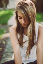 Teen girl sitting outside.