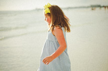 a young girl on a beach in a sundress