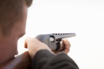 a man pointing a shotgun