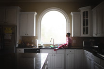 a little girl looking out a window sitting on a kitchen countertop