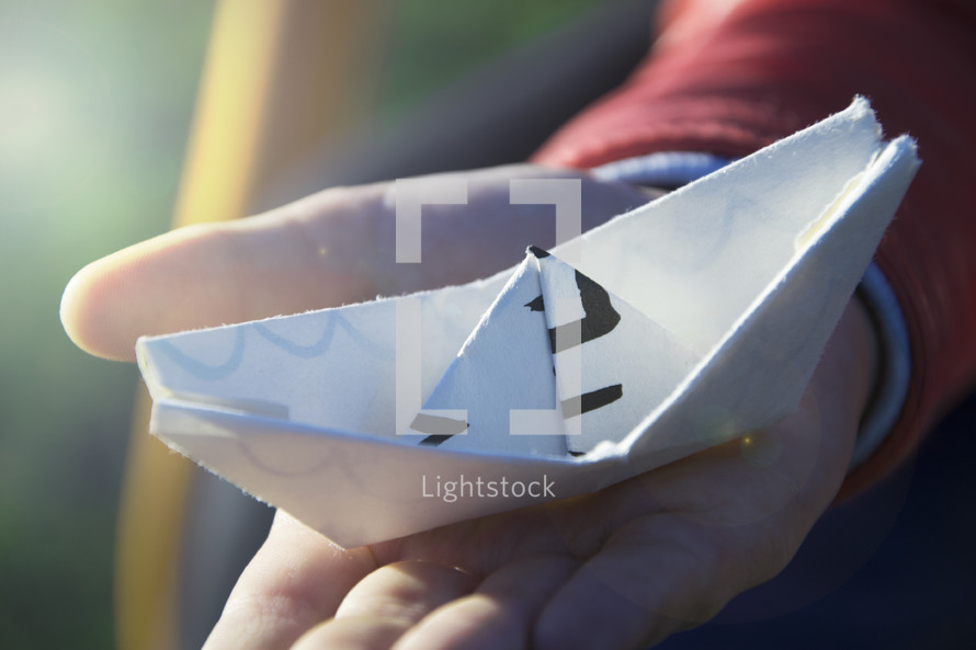 child holding a paper boat