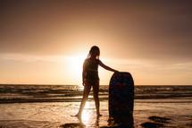 a girl with a boogie board on a beach