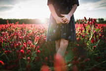 a girl standing in a field of red flowers