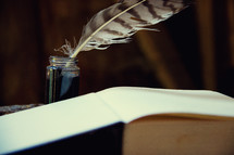 quill pen and ink with open Book