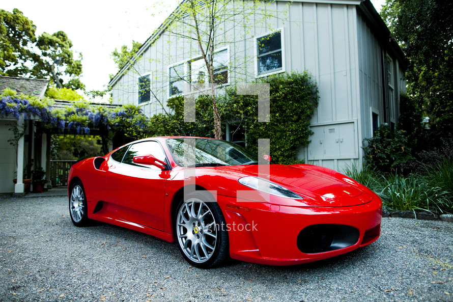 Red ferrari  fast car exotic parked at house in gravel  driveway.