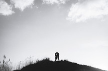 a couple kissing at the top of a hill
