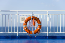 A life preserver hanging on the railing at the end of a ship