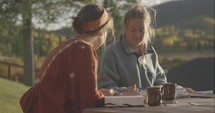 teen girls sitting outdoors discussing scripture