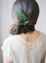 a woman with a fern twig in her hair