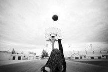 Girl shooting basketball into hoop