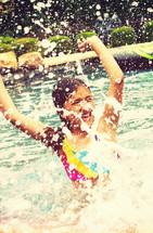 girl child splashing in a pool