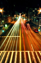 A long exposure photo taken of cars driving along a road in New York City.