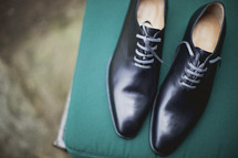 A pair of black dress shoes on a chair