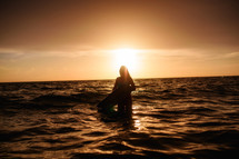 silhouette of a female surfer in the ocean at sunset