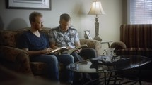 father and adult son reading a Bible together