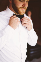 a man fixing his bow tie