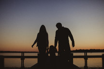silhouette of a mother and father holding hands with their daughter walking on a dock