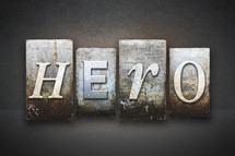 Stone tiles spelling the word HERO.