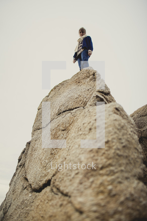 woman standing at the edge of a rock