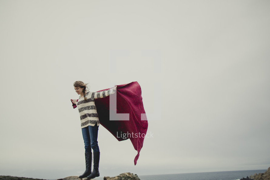 woman standing at the top of a rock holding a red blanket